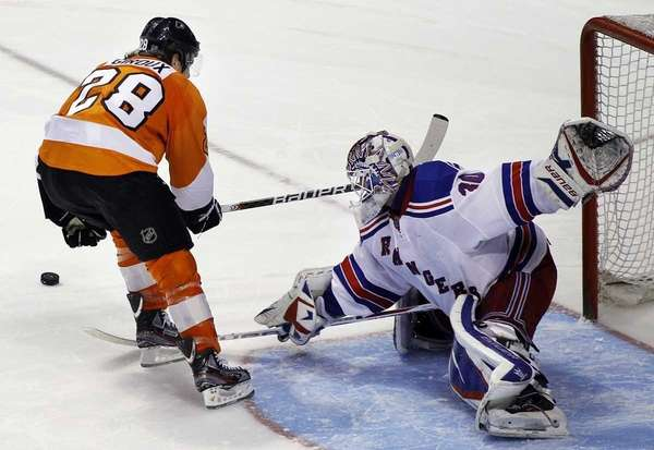 New York Rangers goalie Henrik Lundqvist, right, deflects
