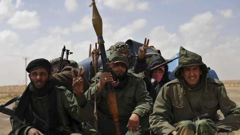 Libyan rebels ride in the back of a