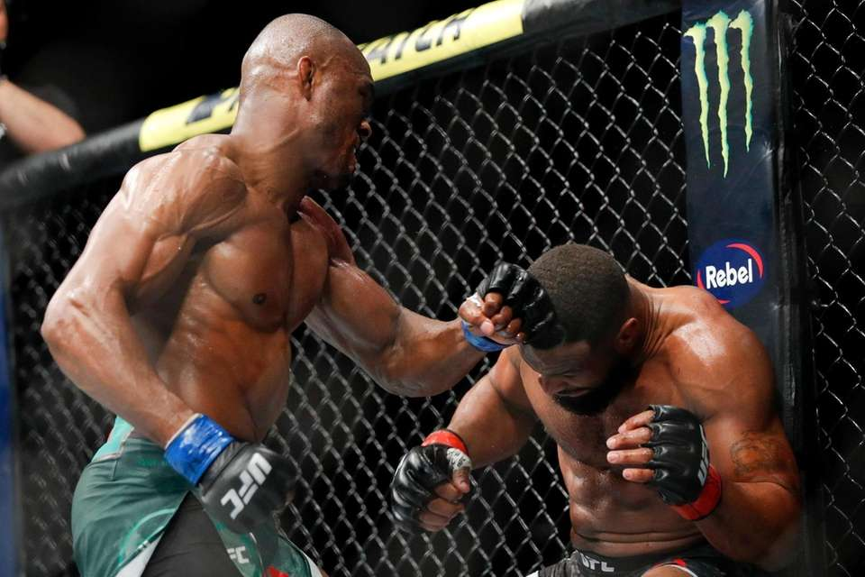 Kamaru Usman, left, hits Tyron Woodley during a