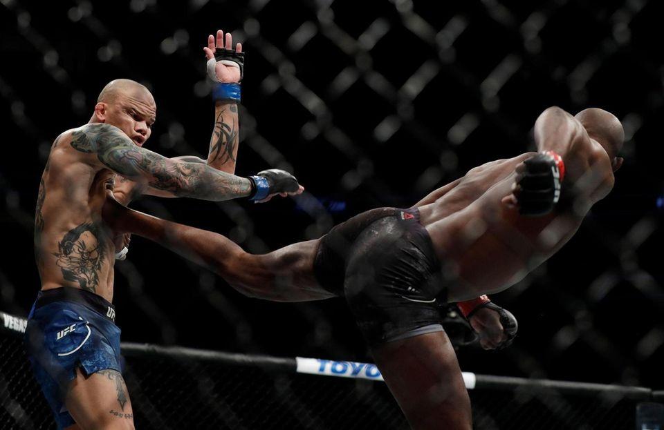Jon Jones (R) lands a kick on Anthony
