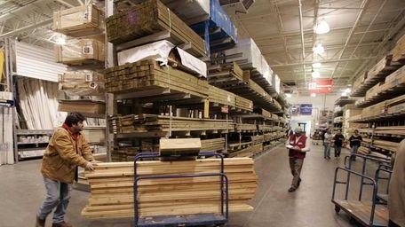 A shopper pushes a cart of lumber through