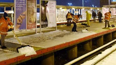 Workers shovel snow at the Ronkonkoma LIRR station