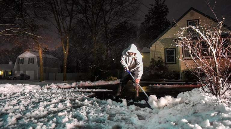Nick Augusta shovels snow and slush in front