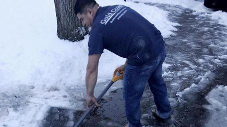 Cristhian Ramos, 30, of Huntington, shovels his driveway