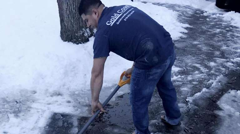 Cristhian Ramos, 30, of Huntington, shovels his driveway
