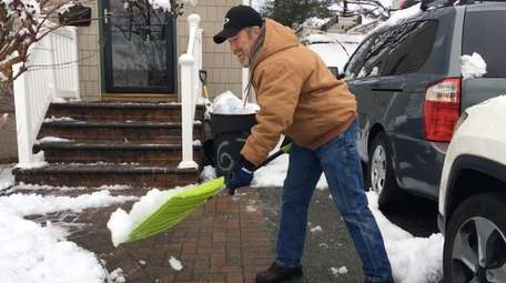 John Glasgow shovels his driveway in Hicksville on