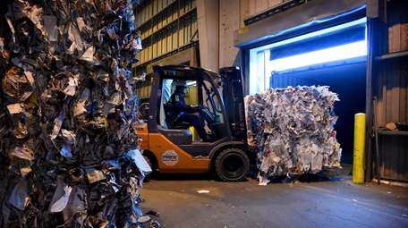 Bales of recyclable paper are loaded onto a