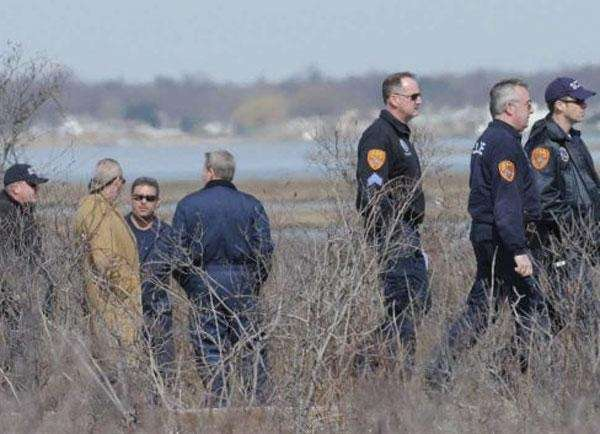 Detectives and investigators probe an area west of