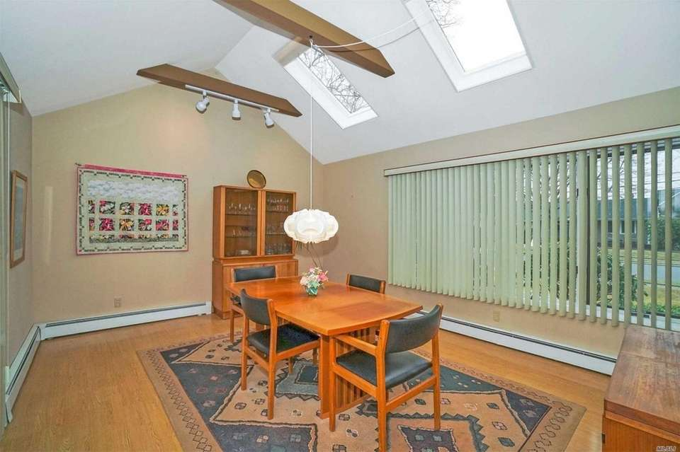 The dining room features vaulted ceilings with skylights.