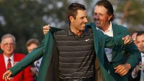 Former champion Phil Mickelson, back, helps Charl Schwartzel