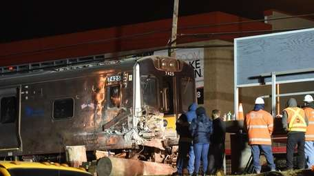 Workers with the rerailed LIRR train involved in