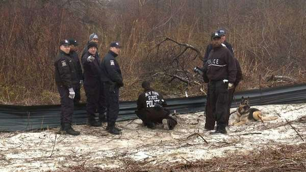 State Police and other investigators examine an object