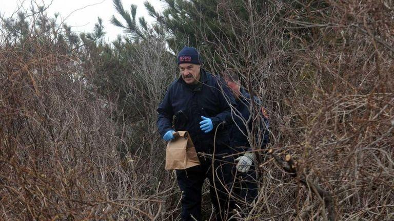 Nassau County police crime scene investigators remove a