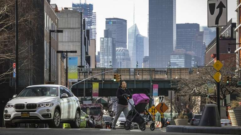 A woman pushes a stroller through Long Island
