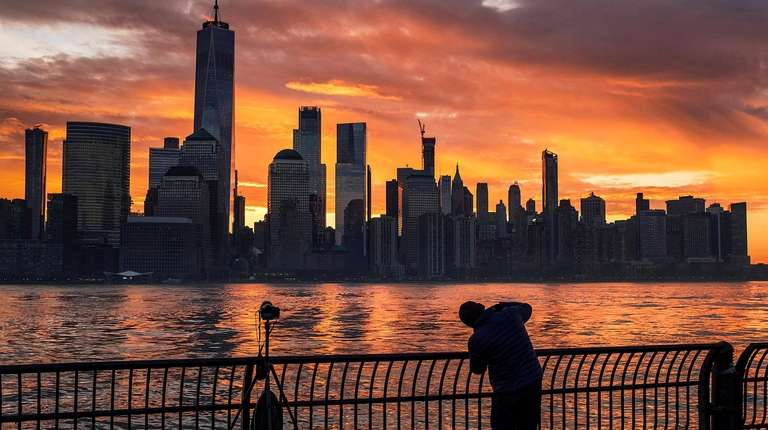 A photographer captures the sunrise behind the New
