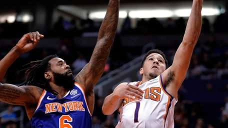 Suns guard Devin Booker shoots next to Knicks