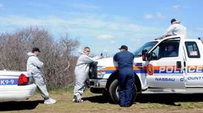 Nassau County Police pause near a wooded area