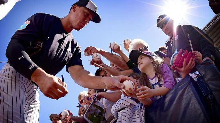 Aaron Judge of the Yankees signs autographs for