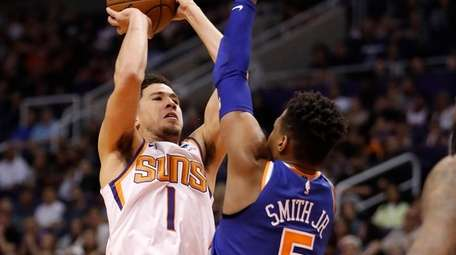 Suns guard Devin Booker shoots over Knicks guard