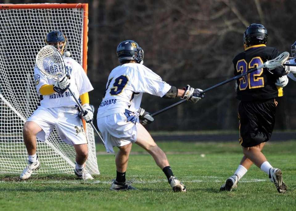 Sayville's Zach Sirico (32) shot is stopped by