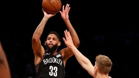 Allen Crabbe takes a three-point shot against the