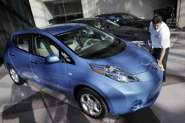 A worker dusts a Nissan Leaf before it