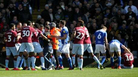 A fan is removed after attacking Aston Villa's