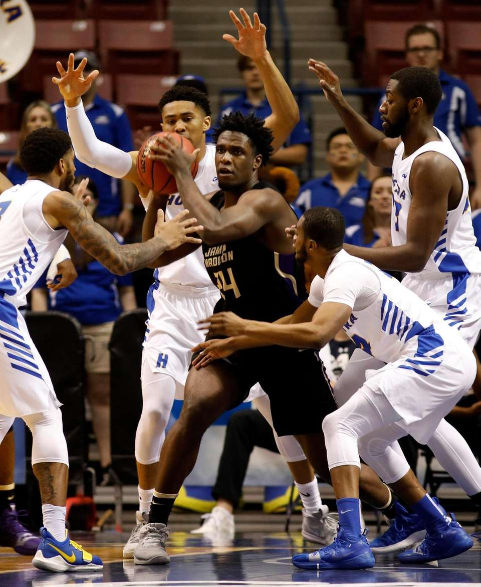 Hofstra's defense surrounds James Madison's Dwight Wilson, center,