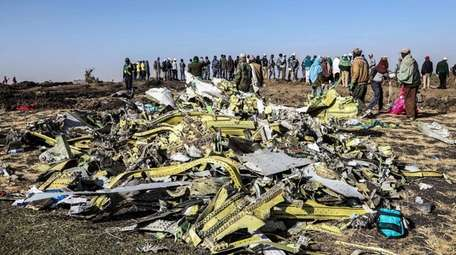 People stand near collected debris at the crash