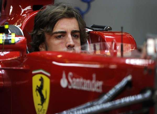 Ferrari driver Fernando Alonso of Spain checks his