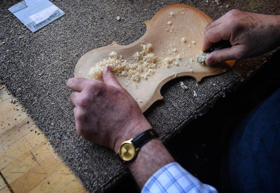 Master violin maker Charles Rufino uses a tiny