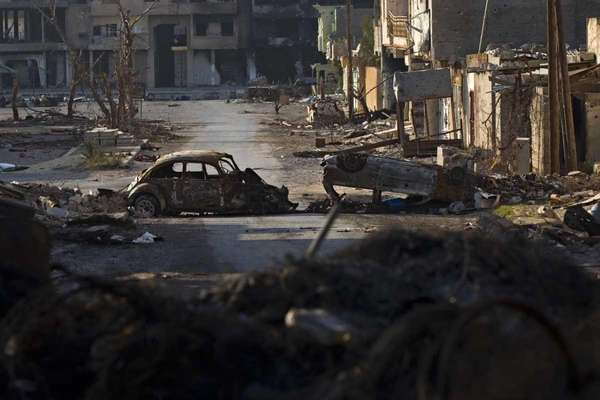 Destroyed cars and buildings are seen in the