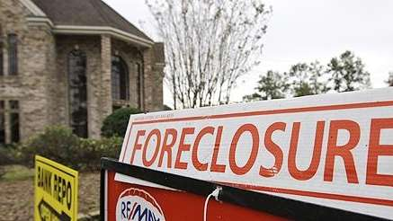 A house is marked with a foreclosure sign.