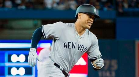 The Yankees' Giancarlo Stanton rounds the bases after