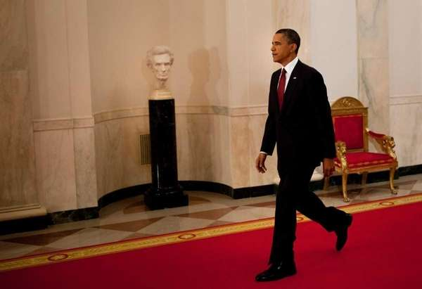 President Barack Obama walks through the Cross Hall