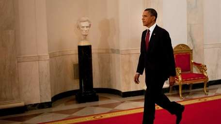 President Barack Obama walks through the Cross Hall