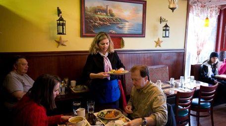 A waitress serves customers at Caf� Taka, a