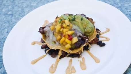A barbecued duck tostada is served with black