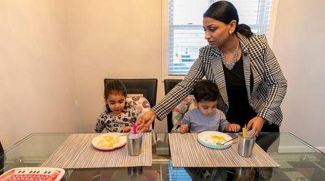 Asma Malik, 30, serves her children Amirah, 3,
