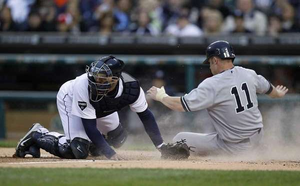 The Yankees' Brett Gardner scores a run past
