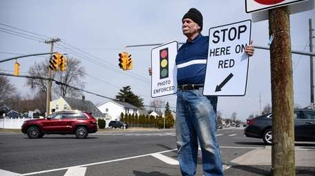 Andy Kuzma of Levittown holds signs required to