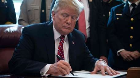 President Donald Trump signs the first veto of
