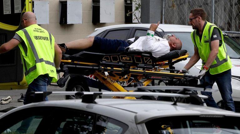 Ambulance staff take a man from outside a