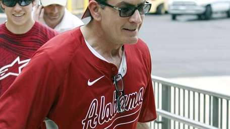 Actor Charlie Sheen helps carry coolers full of