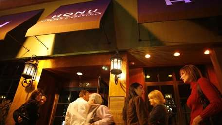 Patrons are seen standing outside of the Honu