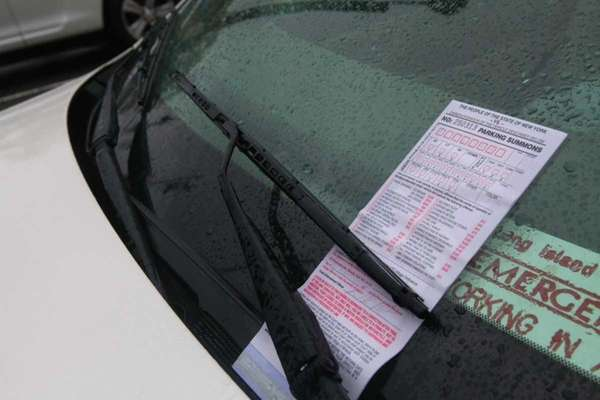 A parking ticket on the windshield on a