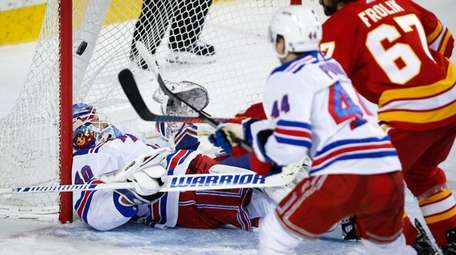 Rangers goalie Alexandar Georgiev, left, is caught on