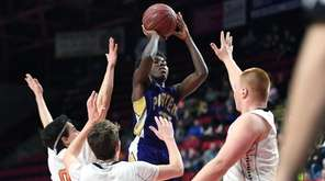 Greenport's Ahkee Anderson takes a shot over three