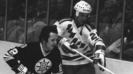 The Bruins' Brad Park, left, skates beside the