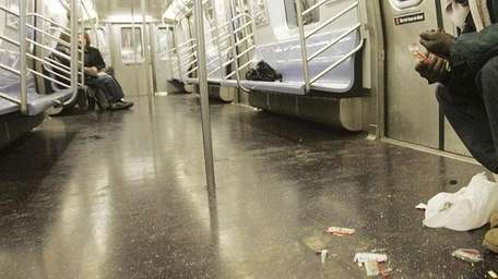 A subway car is littered by trash